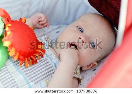 baby with fingers in mouth laying in stroller - stock photo