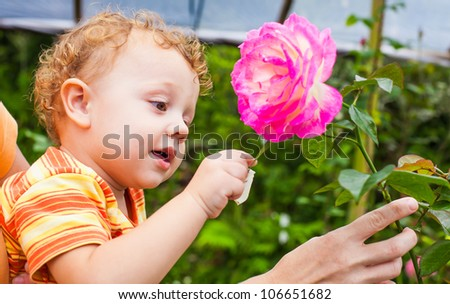 baby with flower in hand - stock photo