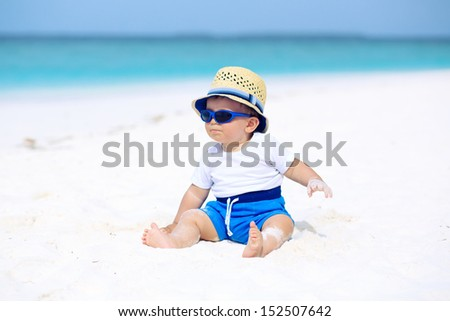 Baby with hat and sunglasses sitting on the tropical beach - stock photo