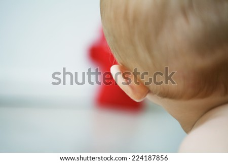 Baby with head turned toward toy, rear cropped view, close-up - stock photo