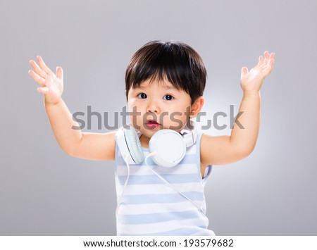 Baby with headphone and hand up - stock photo