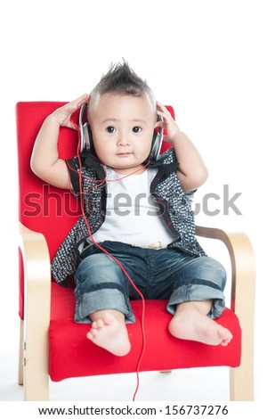 baby with headphone sitting on chair