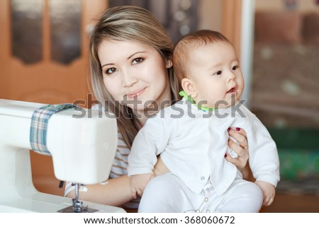 Baby with his mother at home, natural light, curiously looking directly into the camera. Near the sewing machine. Child care and work at home, babysitter. - stock photo