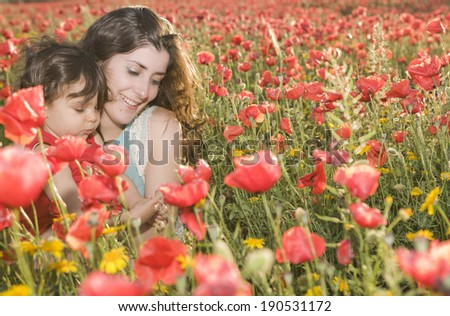 baby with mother enjoying a field day outdoors - stock photo