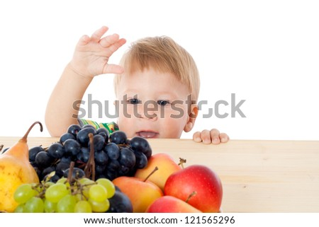 Baby with pile of fruit on the table, isolated on white - stock photo