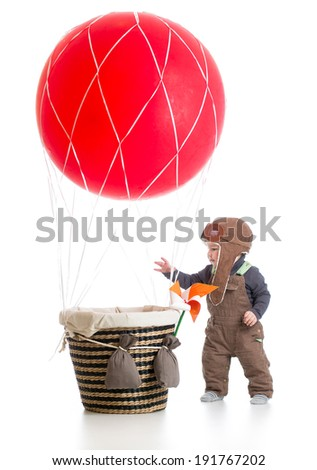 baby with pilot hat on hot air balloon - stock photo