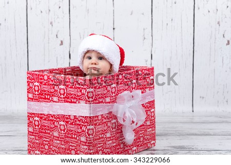 baby with red cap sitting in xmas giftbox