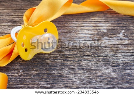 baby yellow soother with ribbon frame on wooden table background - stock photo