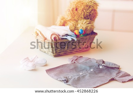 babyhood, motherhood, clothing and object concept - close up of baby clothes and toys for newborn boy in basket at home - stock photo