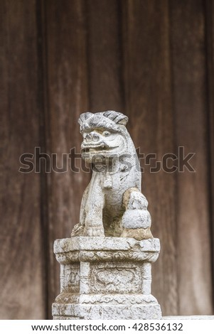 BAC NINH, VIETNAM - JULY 25, 2015 - Small statue at the entrance to But Thap Pagoda with a demon or lion on a decorated pedestal with a flower motif