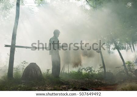 Bac Ninh, Vietnam - May 29, 2016: Fisherman mending fish net by Cau river under heavy smoke from discard rice straw fire