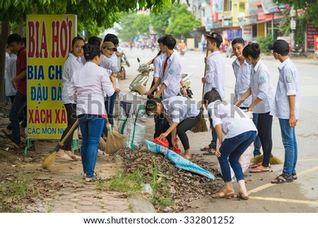 Bac Ninh, Vietnam - Sep 9, 2015: Group of high school students cleaning street in front of their school within the volunteer event for saving environment