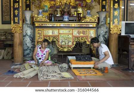Bac Ninh, Vietnam - Sep 12, 2015: Senior craftsmen making printed painting artwork in traditional way in Dong Ho village. Famous Dong Ho paintings has become aesthetic symbol of Vietnamese culture.
