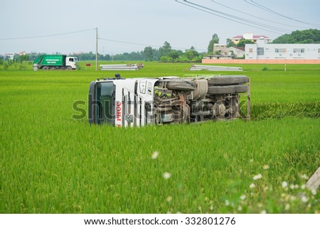 Bac Ninh, Vietnam - Sep 9, 2015: Turned over car after the traffic accident laying on rice paddy field - stock photo