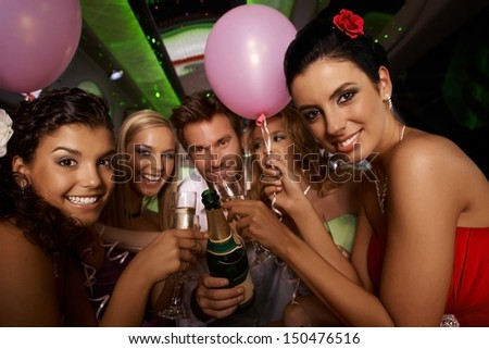 Bachelorette party in limousine with attractive young people, having fun. - stock photo