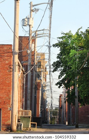 Back alley with lots of electric wires at sunset - stock photo