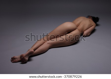 back and butt naked women dark background - stock photo