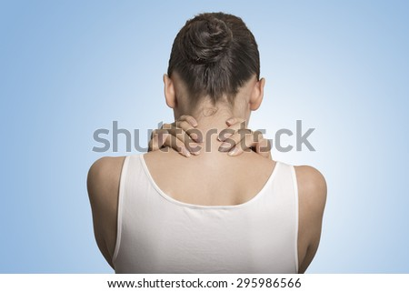 Back and spine disease. Closeup back view tired female massaging her painful neck isolated on blue background  - stock photo