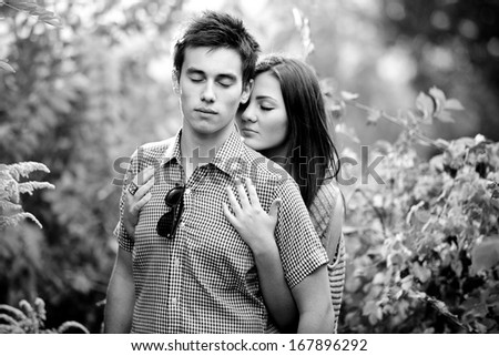 Back and white closeup portrait of young couple hugging with closed eyes at park - stock photo