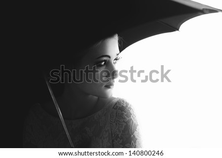 Back and white portrait of a pretty girl mime. Standing under umbrella. - stock photo