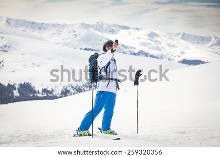 Back country skier making selfie with snowy mountains in the background