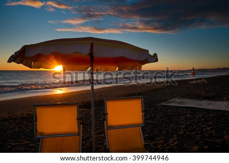 Back-light on pool at sunset with palm trees from Marina di Bibbona, Tuscany