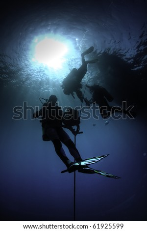 back light view of scuba divers during decompression safety stop. - stock photo
