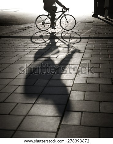 Back lit cyclist in evening light casting long shadow on sidewalk - stock photo