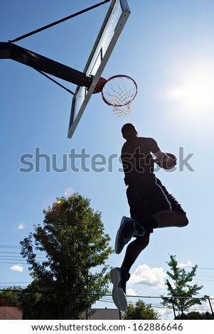 Back lit silhouette of a basketball player going up for a reverse jam. - stock photo