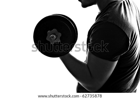 Back lit silhouette of a young man lifting weights in black and white. - stock photo