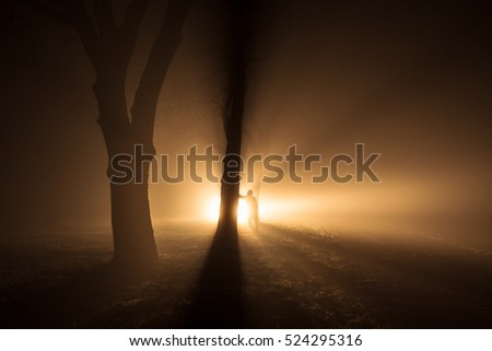 Back lit silhouette of person standing in a forest with light shining through fog
