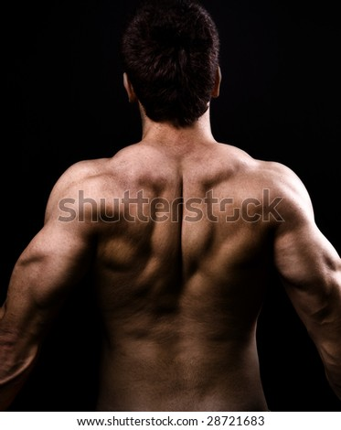 Back muscles of big healthy naked man over black