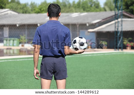 back of a football referee holding the ball - stock photo