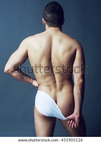 back of a handsome muscular sporty man against dark studio background - stock photo