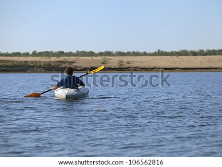 Back of a man rowing in the canoe - stock photo