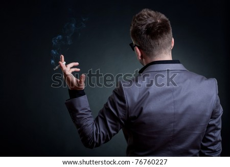 Back of a man with a cigarette in his hand, over dark background - stock photo