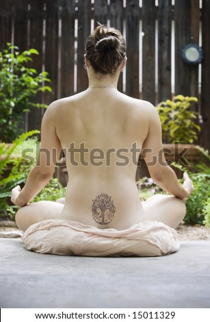 Back of a nude woman with a Yoga tattoo meditating