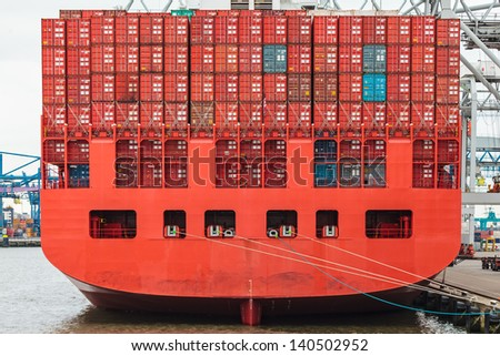 Back of a red container ship filled with red containers in a harbor - stock photo
