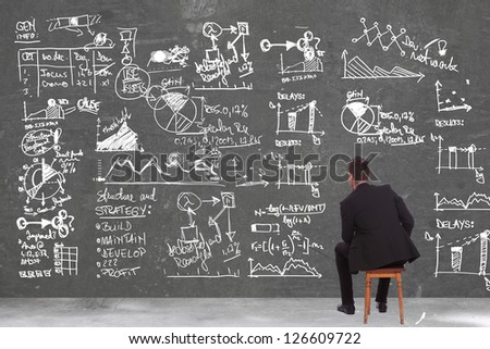 back of a seated pensive business man looking at some calculations on a big wall