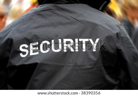 back of a security guard in front of blurred crowd - stock photo