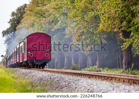 Back of a steam train with a red rail car at the end on a track through beautiful landscape/Railroad Farewell View - stock photo