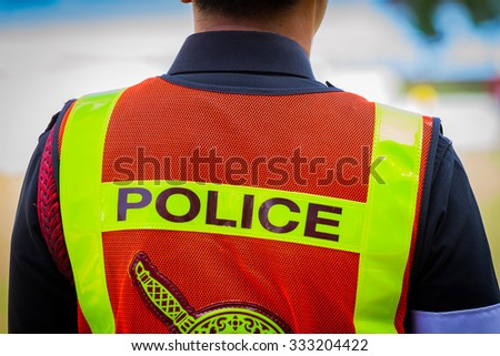 back of a Thai police officer's jacket with the word police written across the back - stock photo