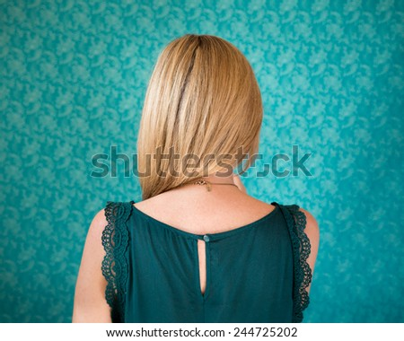 Back of a woman's head standing in front of a wallpapered wall - stock photo