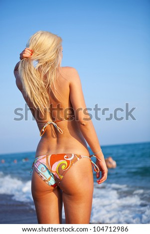 back of a young woman standing on sand near sea looking away - stock photo