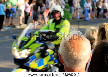 Back of an healthy looking elderly man with white thinning hair and balding sun tanned head. Also a policeman on a motorbike rides past and both look at each other   - stock photo