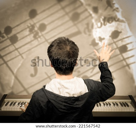 back of asian male musician / pianist / composer arranges music note on imagination - stock photo