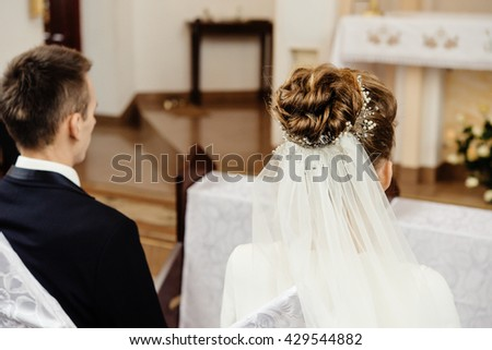 back of bride and groom sitting at wedding ceremony in church, brides luxury hairstyle - stock photo