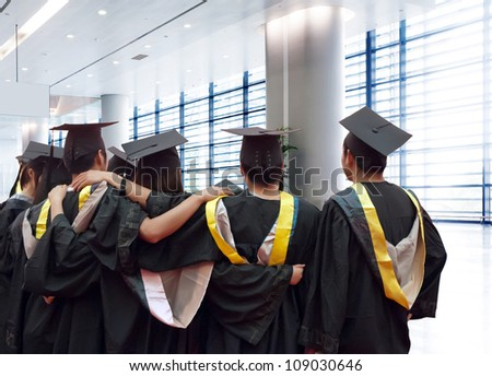 back of chinese graduates with the background of modern architecture - stock photo