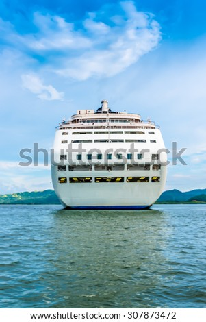 Back of cruise ship, stationary, floating in the ocean with cloudy blue sky and green hills in the background - stock photo