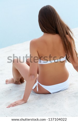 Back of female in white bikini sitting on sandy beach during vacation